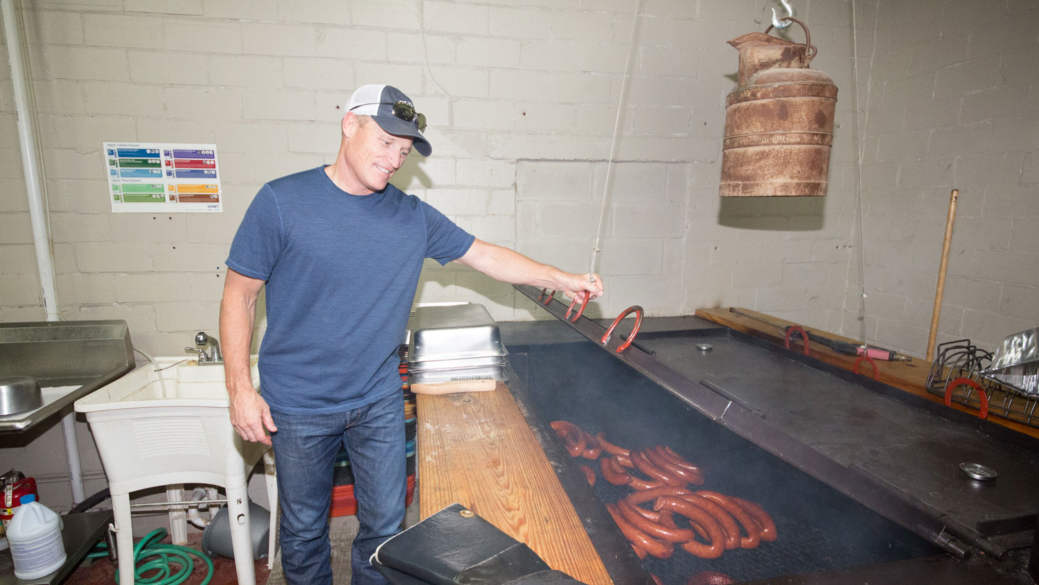 Old 300 BBQ owner Mike Betzer inspects sausage on the grill in the kitchen