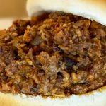 A closeup image of chopped BBQ on a bun